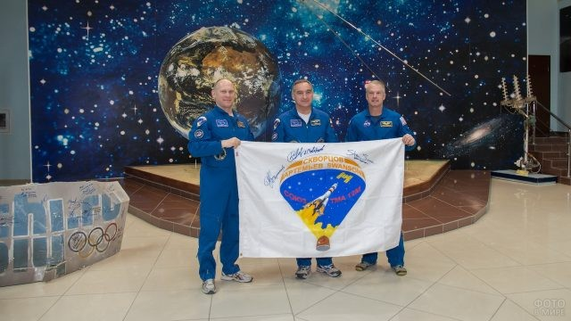 Космонавты держат флаг с автографами