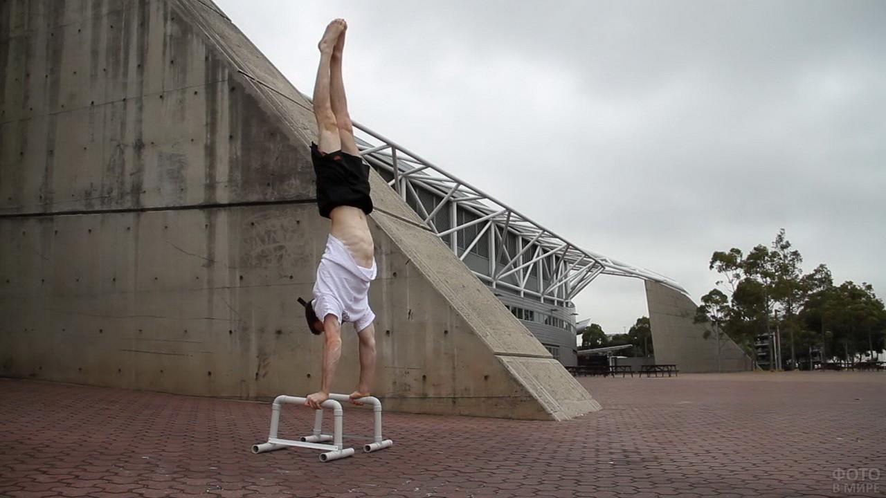Мужчина вверх ногами на тротуаре
