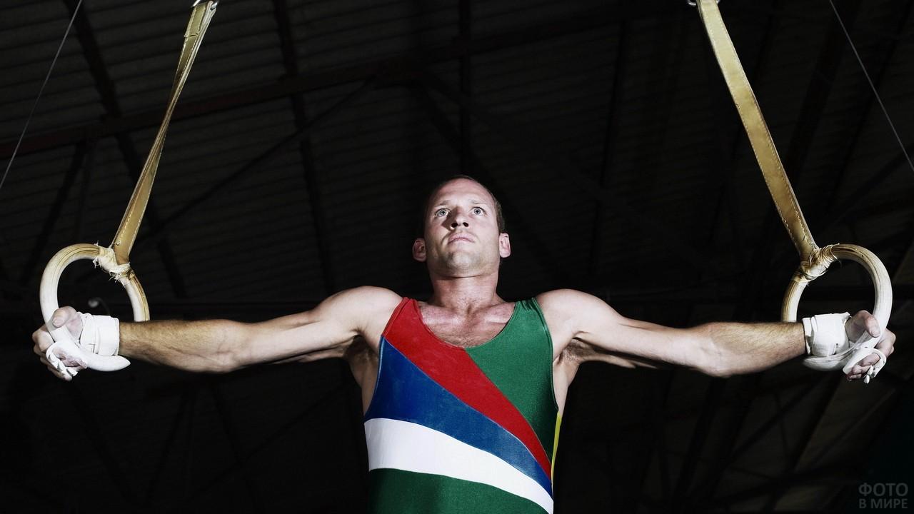Спортсмен на кольцах на вытянутых руках