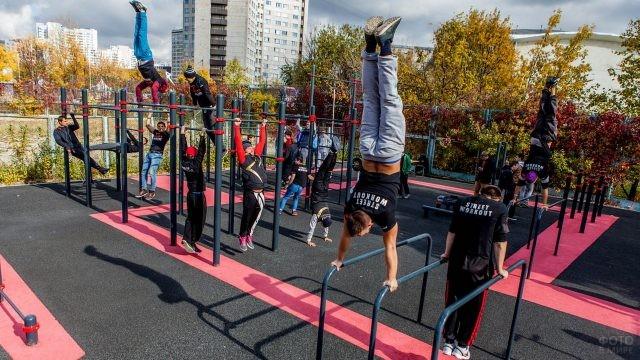 Уличные гимнасты на спортивной площадке