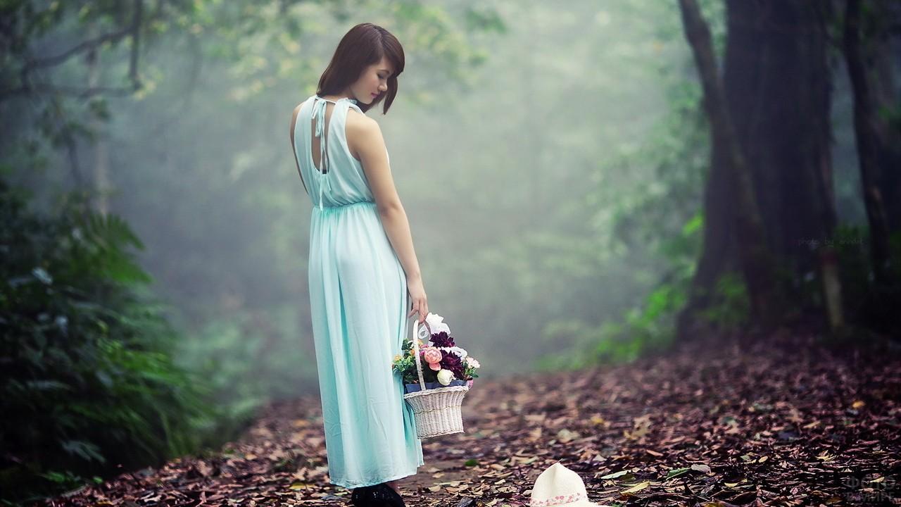 Азиатка с корзиной цветов в лесу