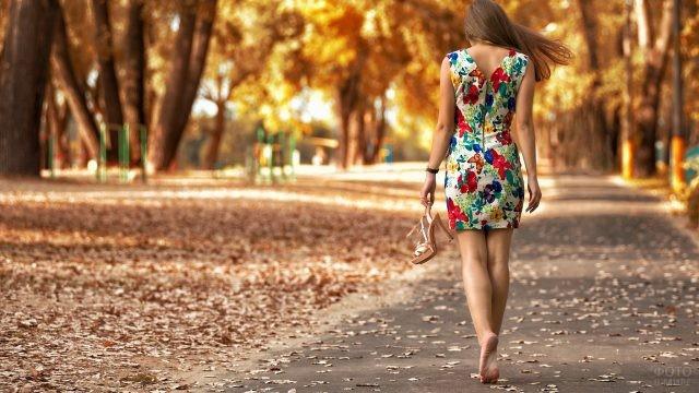Девушка босиком идёт по осеннему парку
