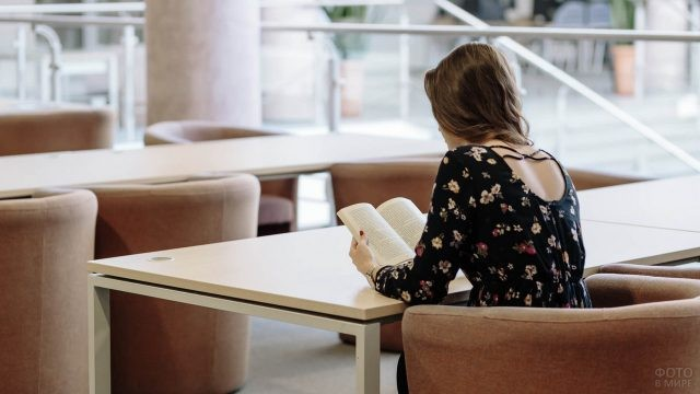 Девушка читает книгу за столом