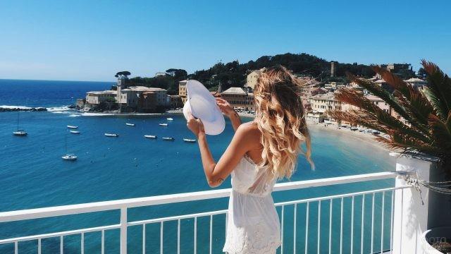 Девушка держит шляпу в руках на террасе