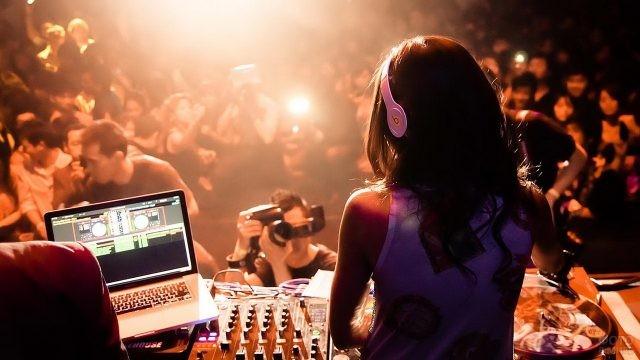 Девушка-диджей за пультом в клубе