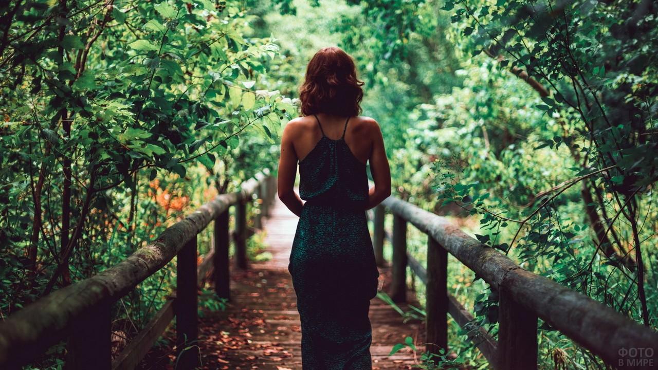 Девушка идёт по деревянному мосту