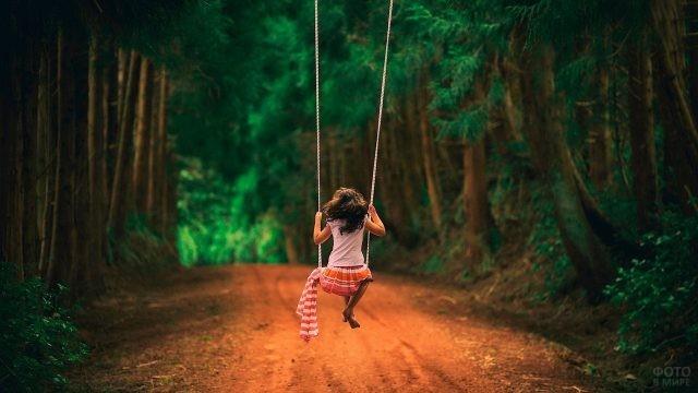 Девушка качается на качелях между деревьями