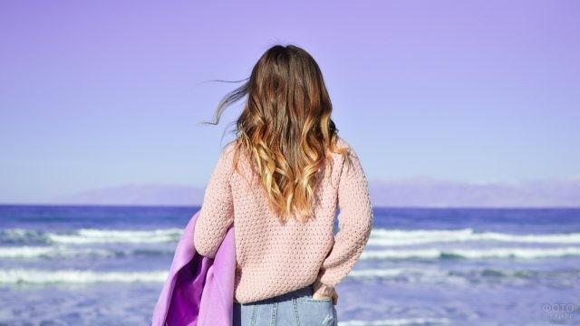 Девушка смотрит на морской прибой
