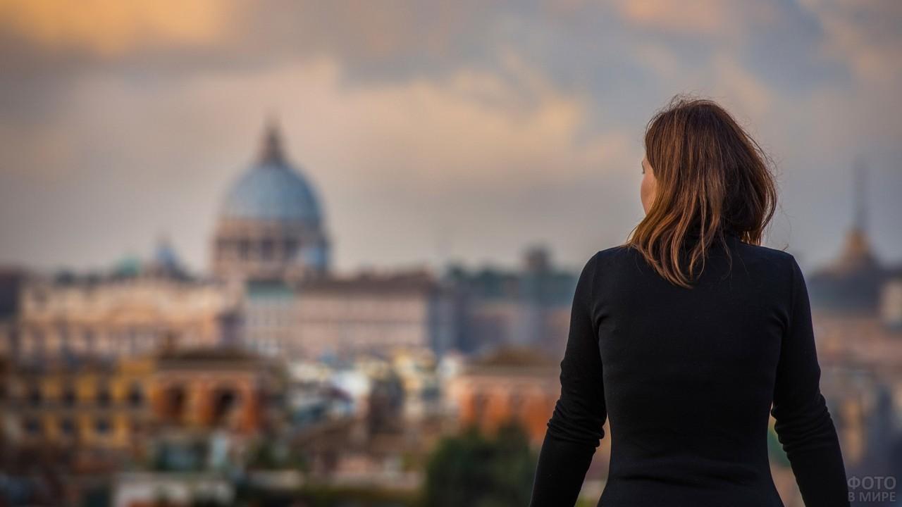 Девушка в чёрной водолазке смотрит на город