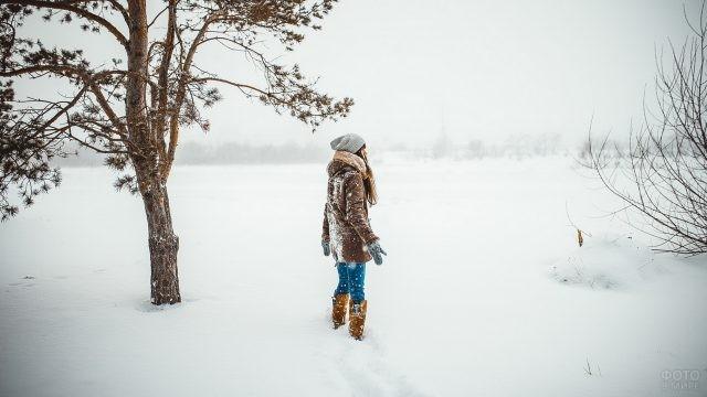 Девушка в снегу возле сосны