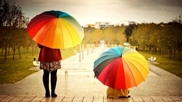 Девушки под разноцветными зонтами в парке