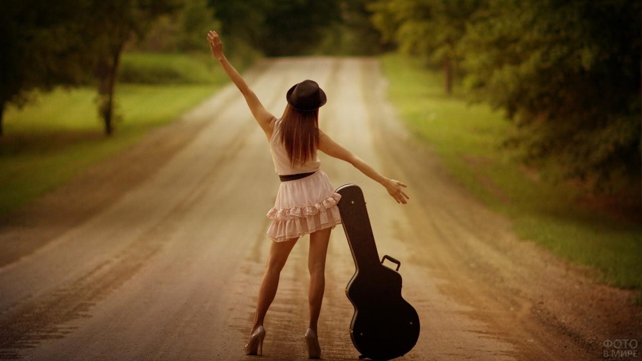 Гитаристка в шляпе на дороге