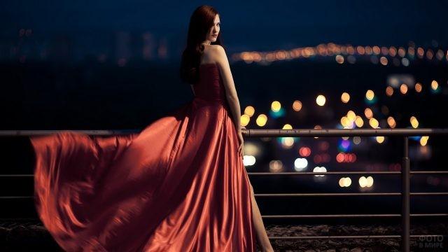 Эффектная девушка в красном на фоне ночного города