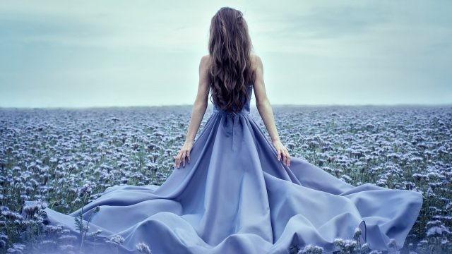 Красавица в голубом платье идёт по полю цветов