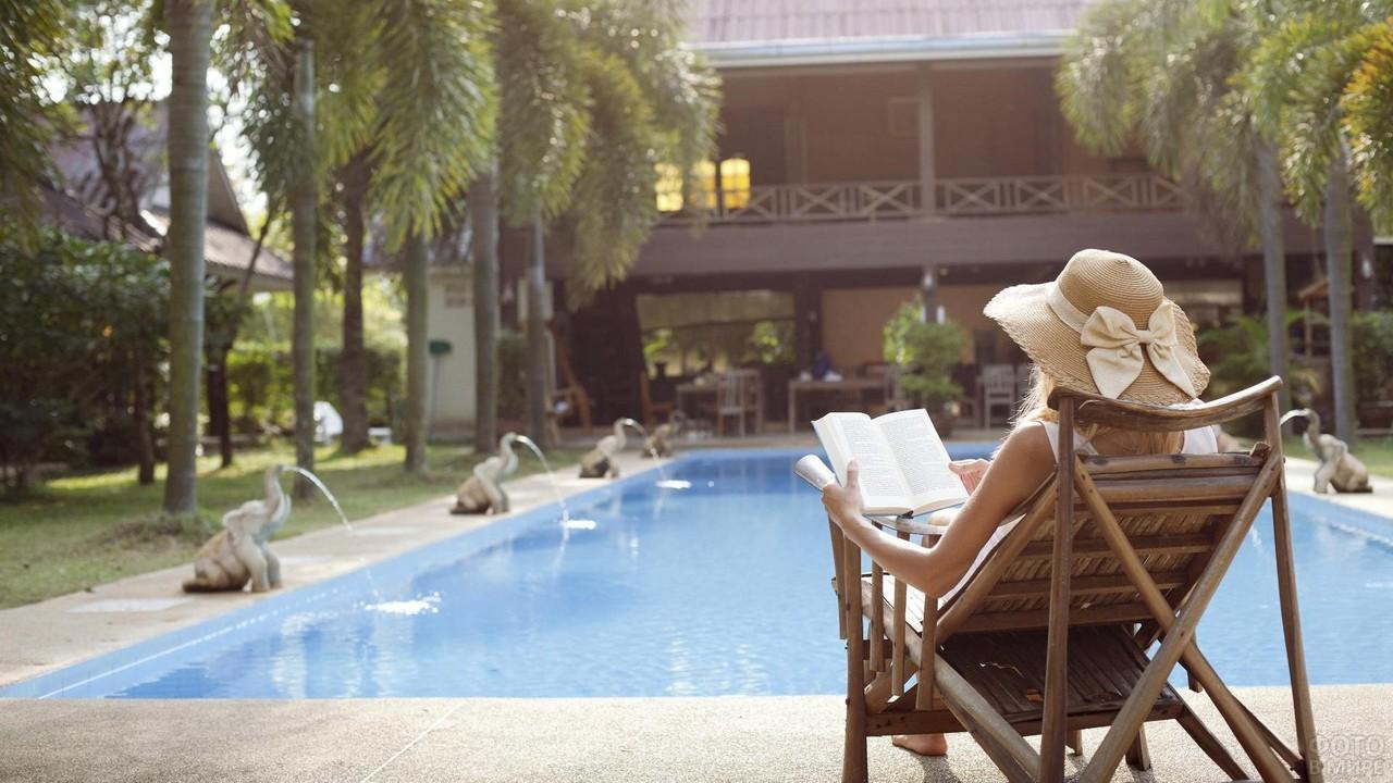 Красотка в шляпе читает книгу у бассейна