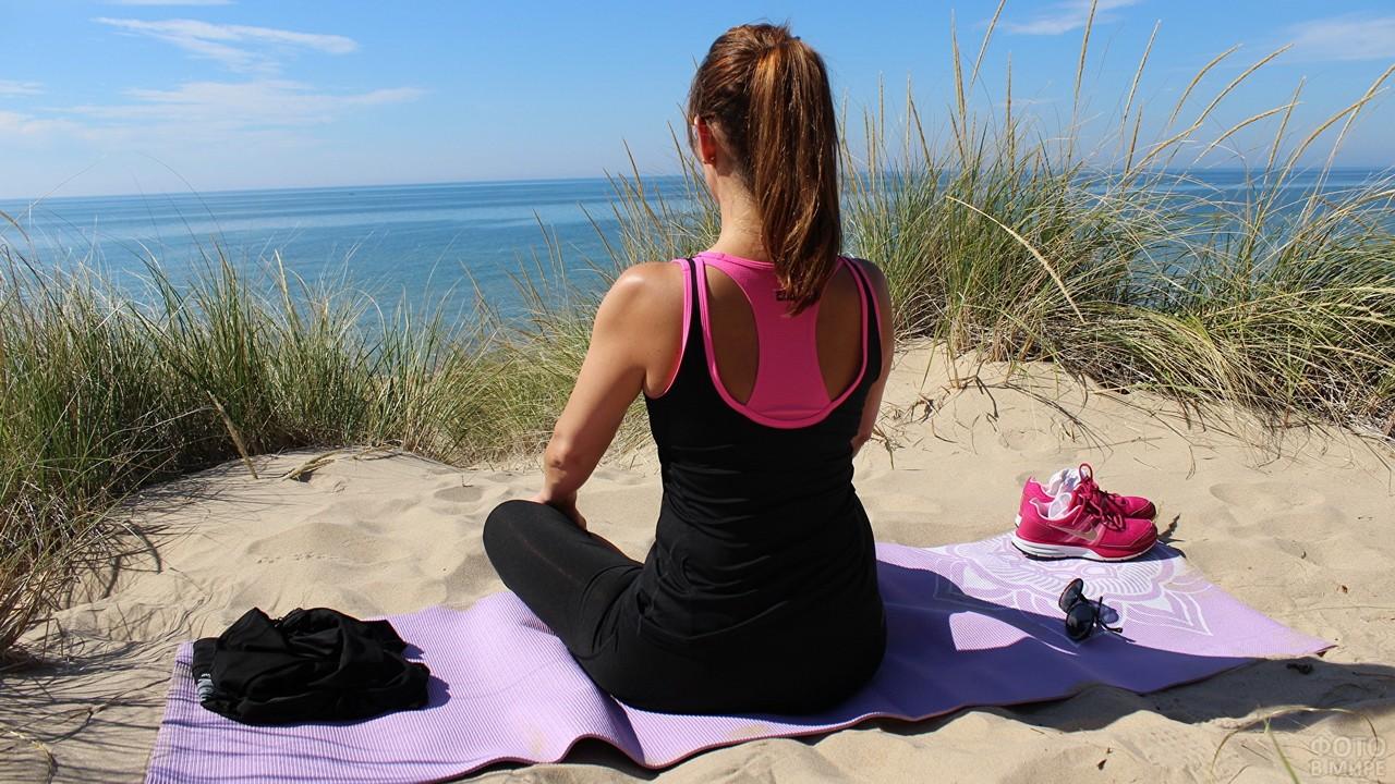 Медитирующая девушка на песке у моря