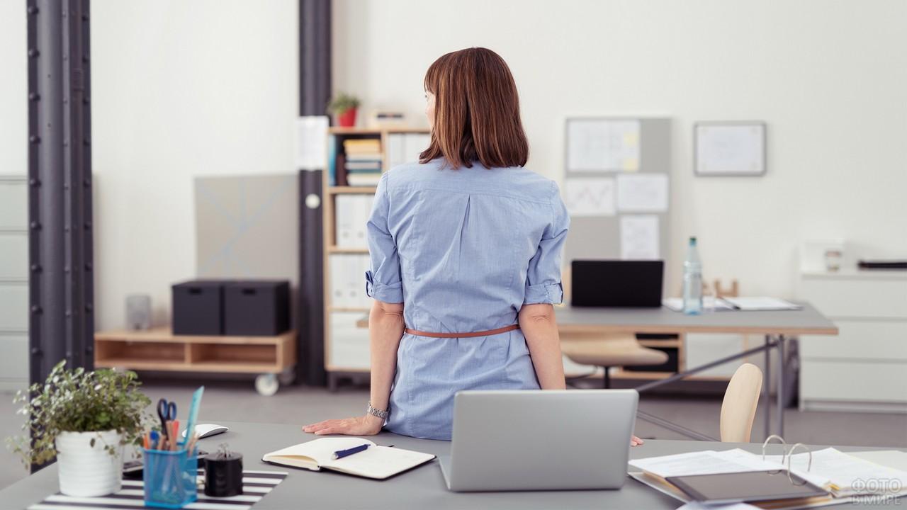 Менеджер сидит на столе в офисе