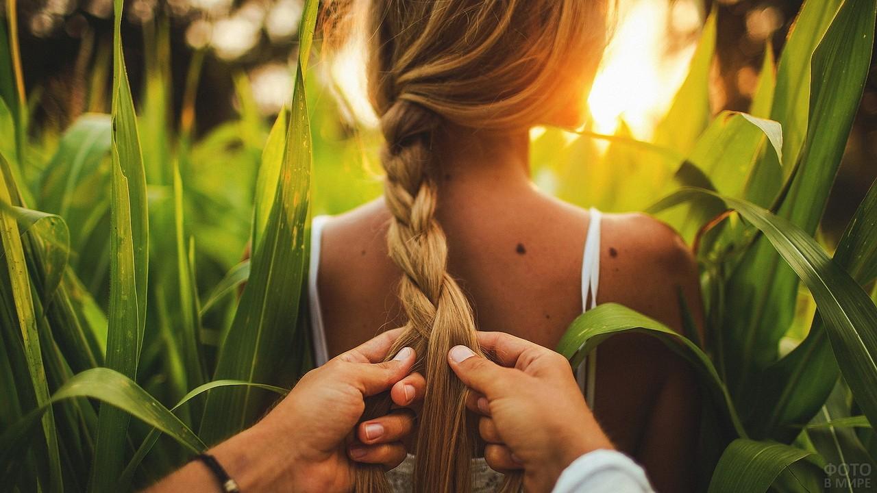 Мужчина заплетает косу девушке