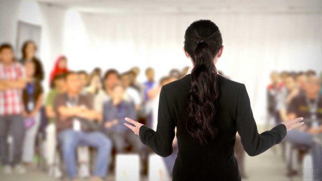 Преподаватель в чёрном костюме на лекции