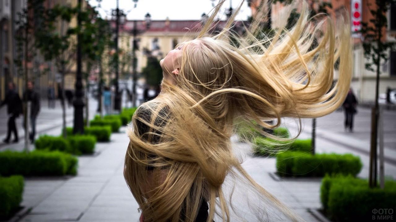 Растрёпанная блондинка с длинными волосами в городе