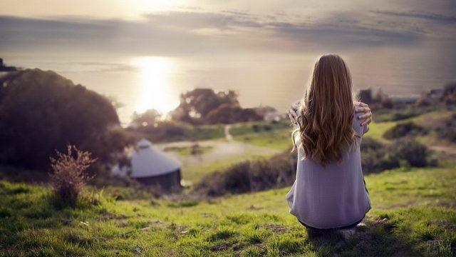 Русоволосая девушка на фоне деревни