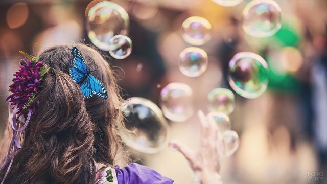 Шатенка с бабочкой в волосах пускает пузыри