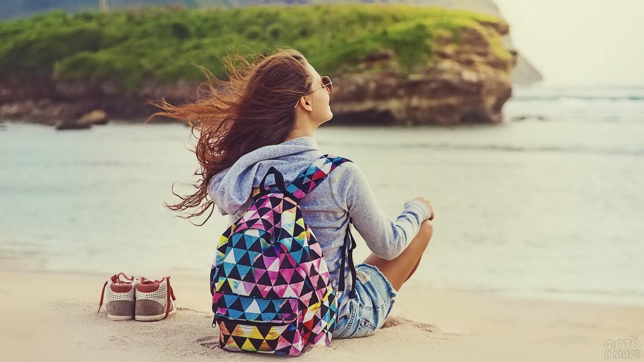 Шатенка с цветным рюкзаком сидит на пляже