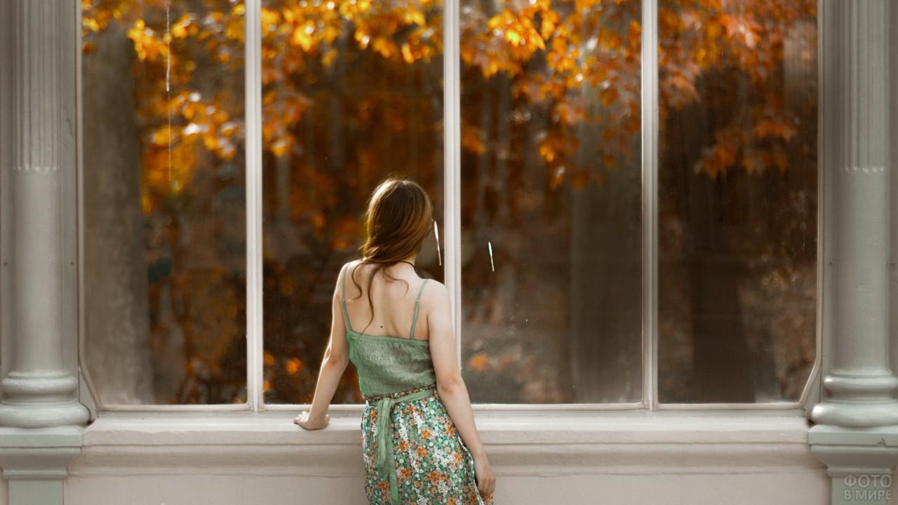 Шатенка смотрит из окна на осенние деревья