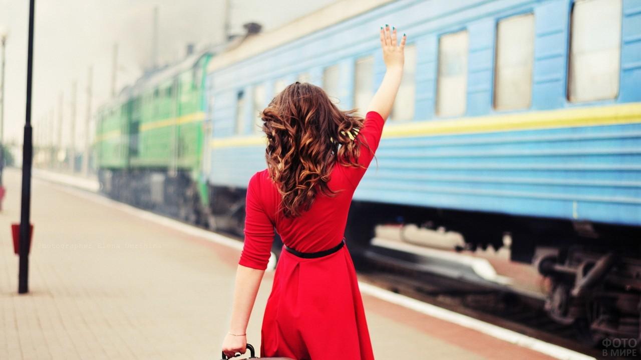 Шатенка в красном платье машет поезду