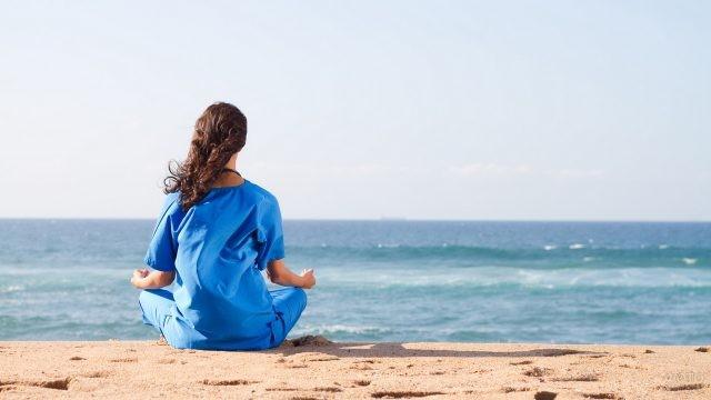 Шатенка в синем костюме медитирует на берегу моря
