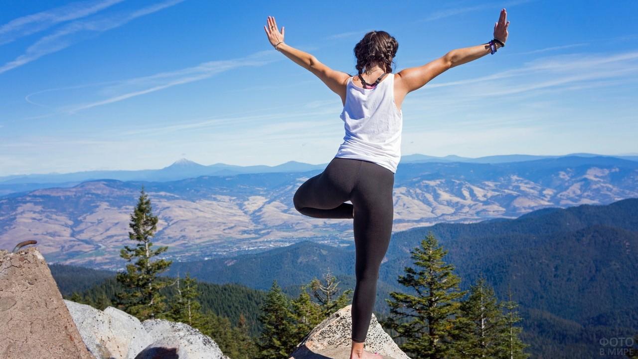 Смелая девушка на вершине гор занимается йогой