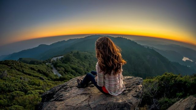 Смелая девушка смотрит на горы с вершины