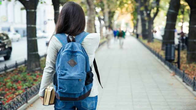 Студенка с рюкзаком и книгами в парке