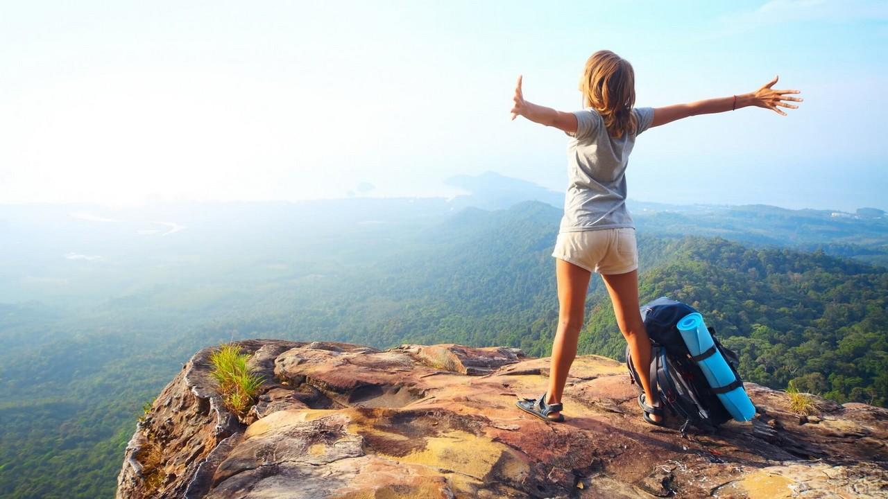 Туристка с рюкзаком на скале