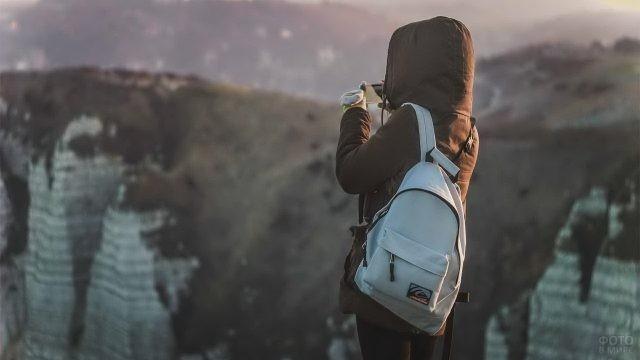 Туристка в куртке фотографирует вид со скалы