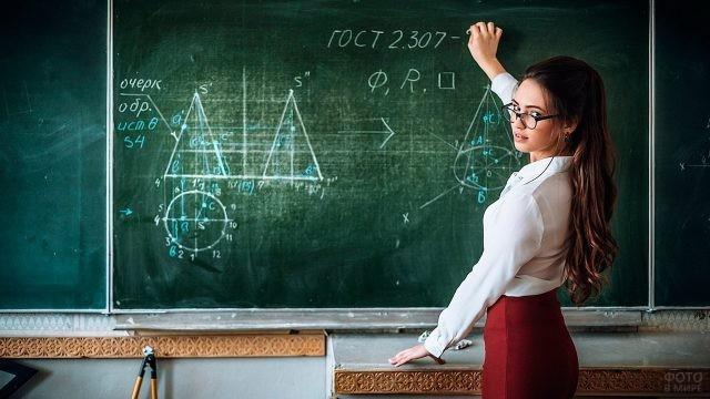 Учительница пишет мелом на доске
