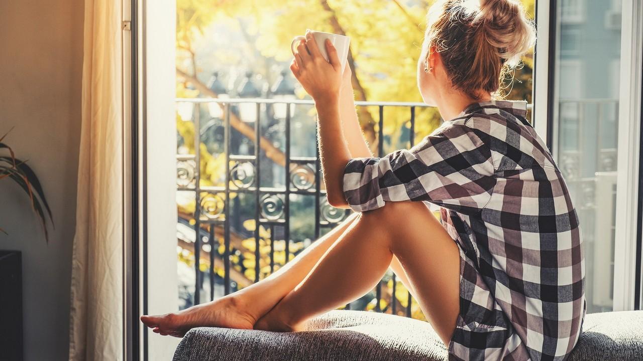 Задумчивая девушка пьёт чай у балкона