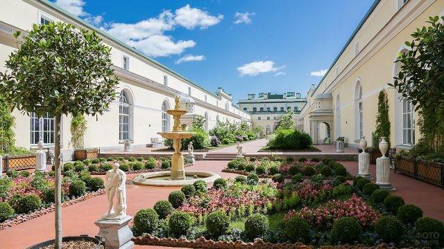 Цветущее патио с фонтанами и скульптурами