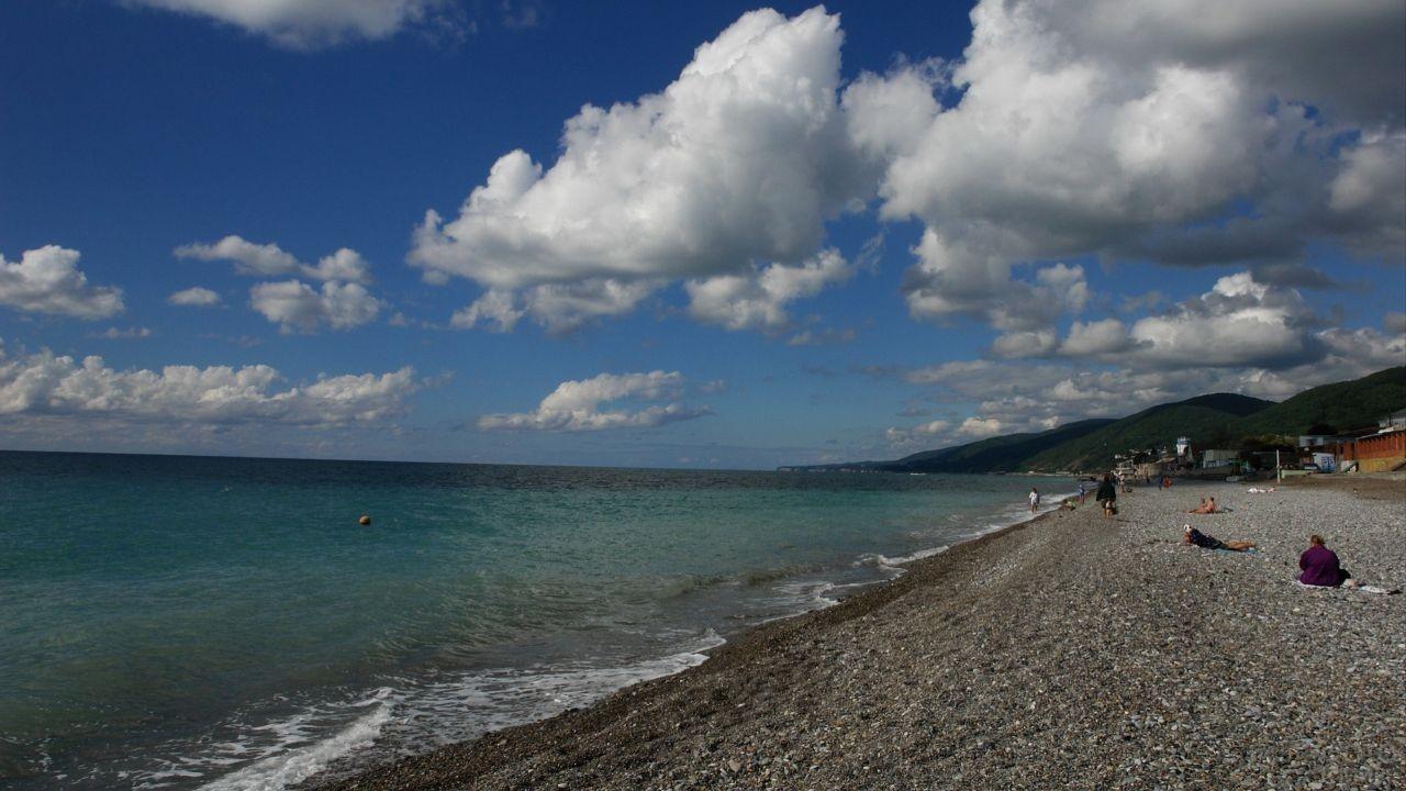 Люди отдыхают на пляже под открытым небом с красивыми облаками
