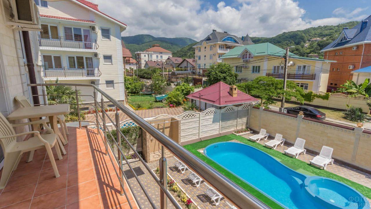 Вид с террасы номера в отеле на гостиничный двор с бассейном