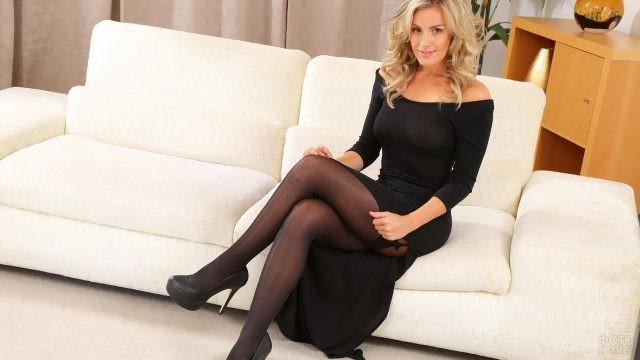 Блондинка в чёрном платье на диване