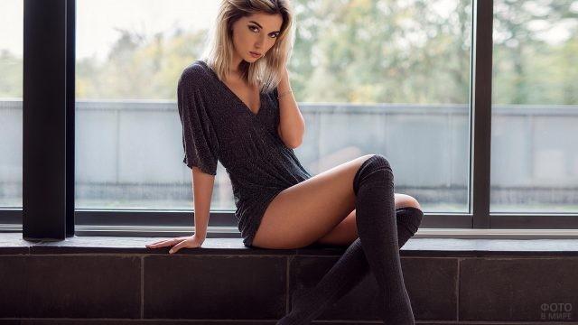 Девушка в сером платье на подоконнике