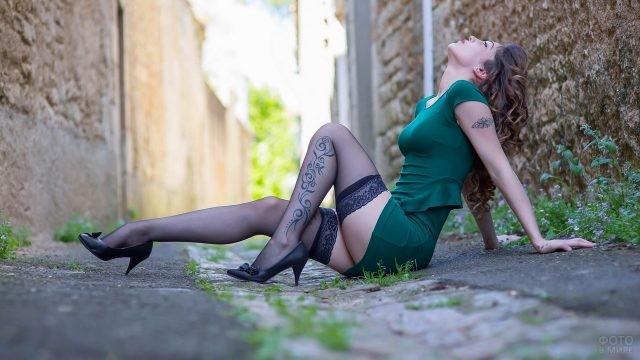 Кудрявая девушка в чулках на асфальте