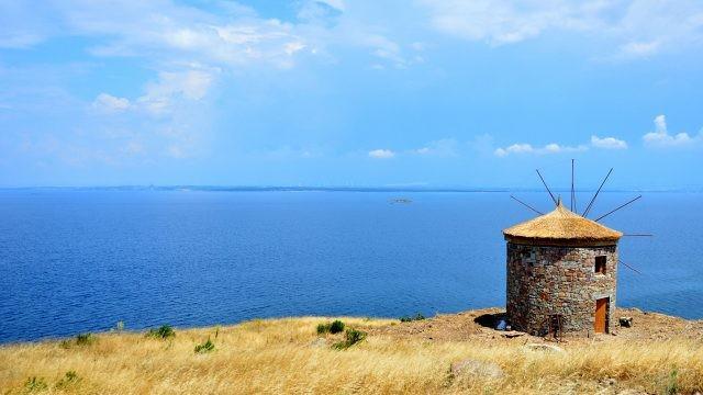 Старинная мельница на фоне моря