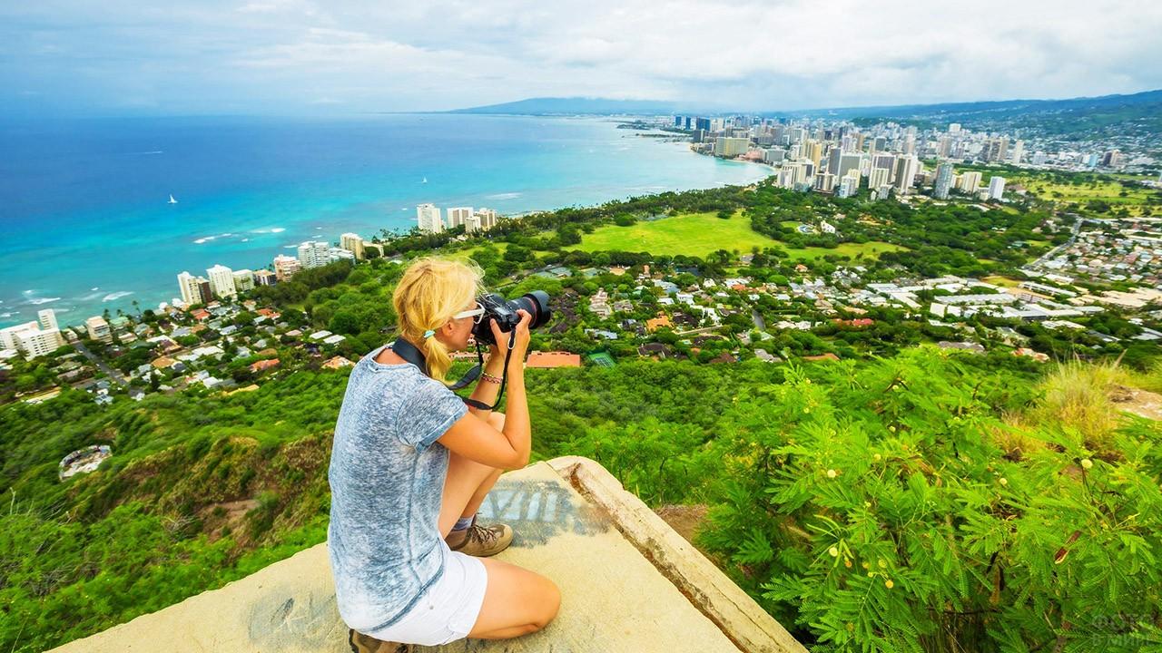 Туристка фотографирует панораму острова Оаху