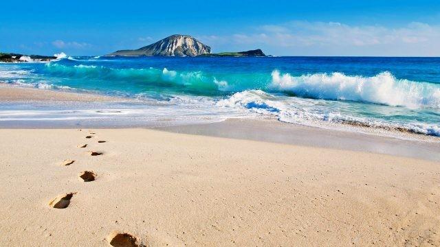 Волны прибоя и следы на песчаном пляже