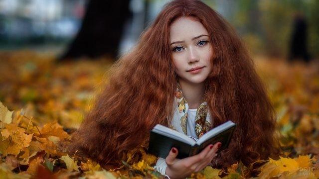 Читающая девушка лежит на осенних листьях