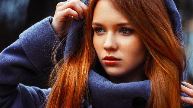 Девушка в синем пальто поправляет капюшон