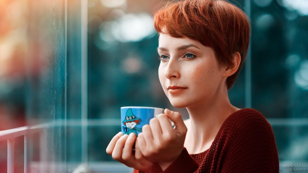Короткостриженная девушка пьёт чай