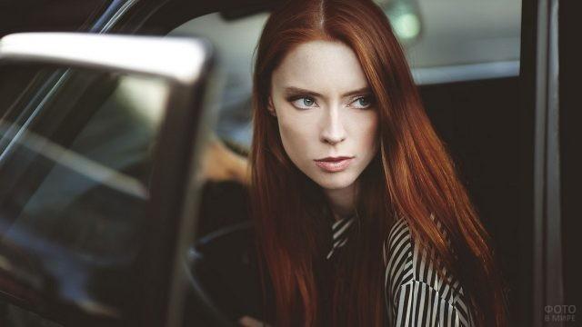 Строгая девушка выходит из автомобиля